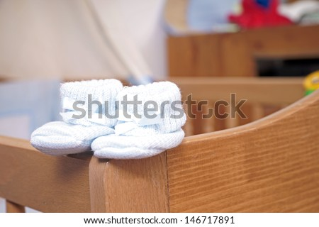 Baby shoes on a Baby bed / baby room - stock photo