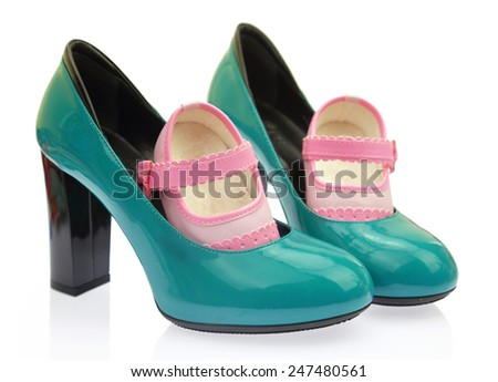 Baby shoes on mom's high heels - stock photo