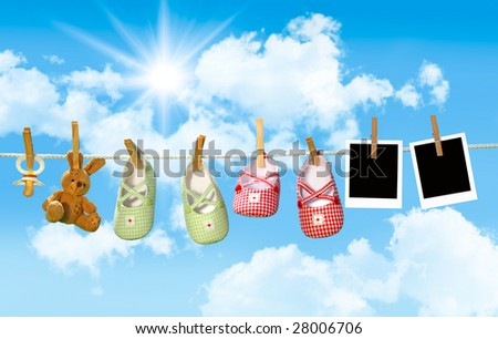 Baby shoes, pacifier and teddy bear on clothesline with blue sky - stock photo