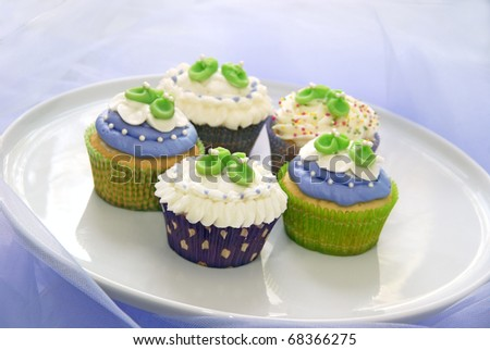 Baby shower cupcakes in purple and green - stock photo