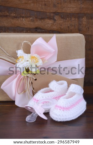 Baby Shower Gift with Booties and Pacifier on Rustic Dark Wood Background.  - stock photo