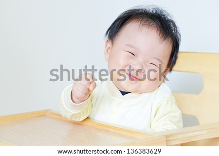 baby sits at a table - stock photo