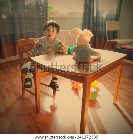 baby sits on chair in interior of the playroom, instagram image style - stock photo