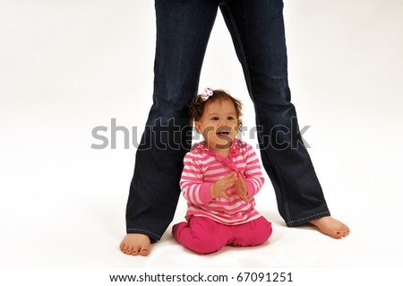 Baby sits on the floor with momm'y standing legs flank her on both sides. Baby looks off to the right, smiling. - stock photo