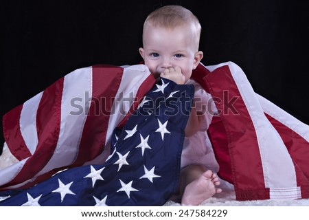 Baby sitting and wrapped by the American flag - stock photo