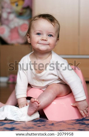 baby sitting at his potty - stock photo