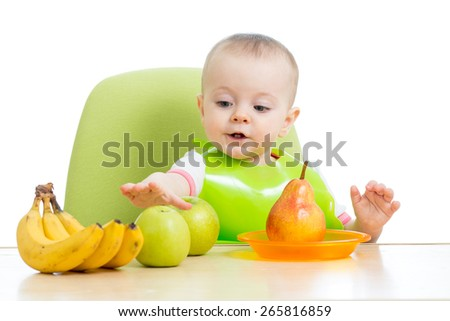 baby sitting at table with fruits isolated