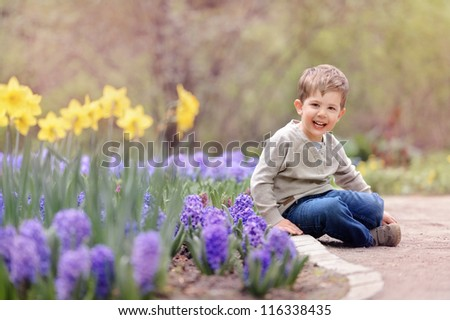 baby sitting by flower beds with beautiful flowers. spring
