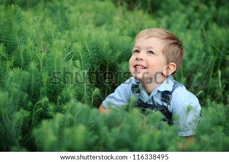 baby sitting in a high green grass and looking up - stock photo