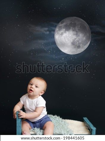 Baby sitting in bed, looking at moon and stars, against a dark blue background. Nap time, sleeping concept