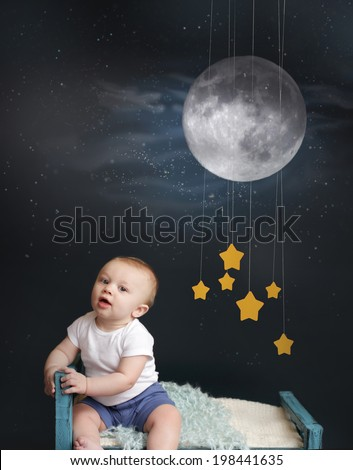 Baby sitting in bed, looking at the moon and stars mobile, starry night. Nap time, sleeping concept