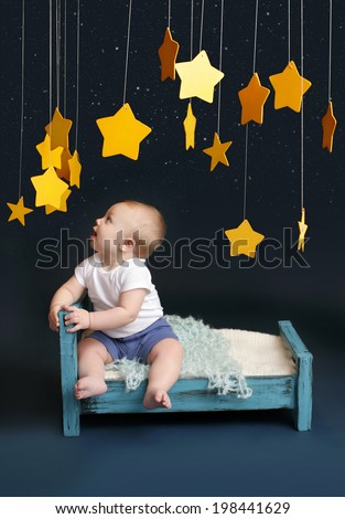 Baby sitting in bed, looking up, against a dark blue background. Nap time, sleeping concept - stock photo