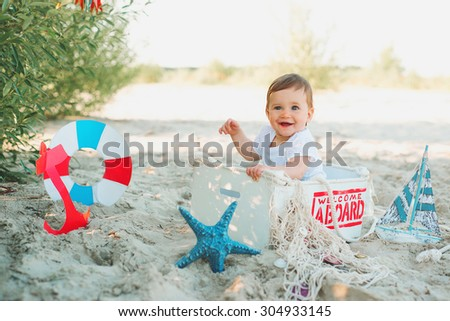 baby sitting in decorate sea box on the beach and smiling - stock photo