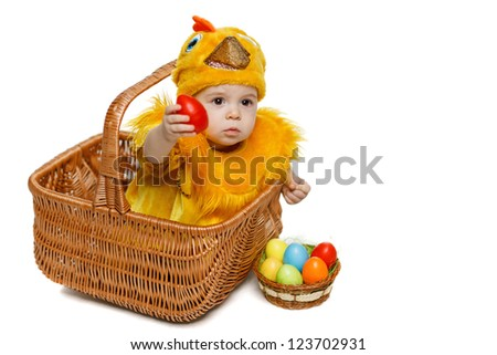 Baby sitting in Easter basket in chicken costume and giving you Easter egg, isolated on white background, with copy space. Easter holiday concept. - stock photo