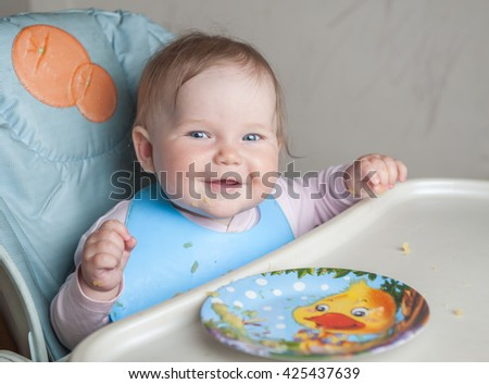 Baby sitting in Feeding table. sitting in chair and eating First solid food for young kid. Fresh organic vegetable lunch. Baby weaning. little girl eat vegetables. Healthy nutrition for children.