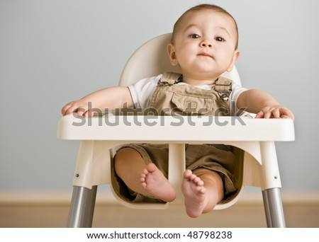 Baby sitting in highchair - stock photo