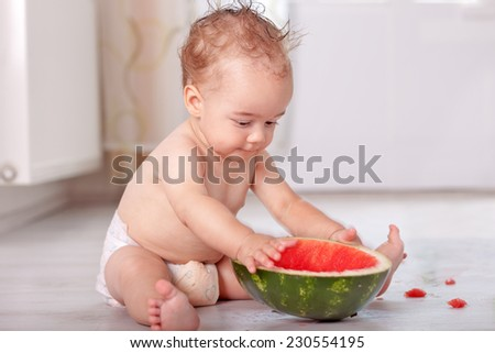 Baby sitting in kitchen eating and playing with watermelon - stock photo
