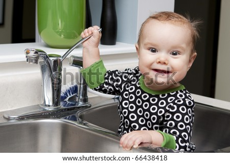 Baby sitting in kitchen sink playing with the tap - stock photo