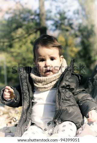 Baby sitting in park - stock photo