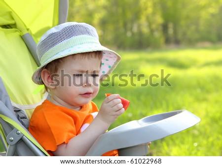 baby sitting in pram eating tomato outdoor - stock photo