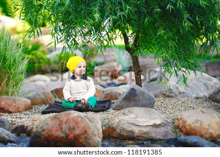 baby sitting in the park  under a tree - stock photo
