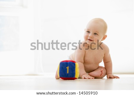 Baby sitting indoors with block smiling