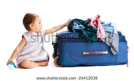 Baby sitting near suitcase with clothes - stock photo