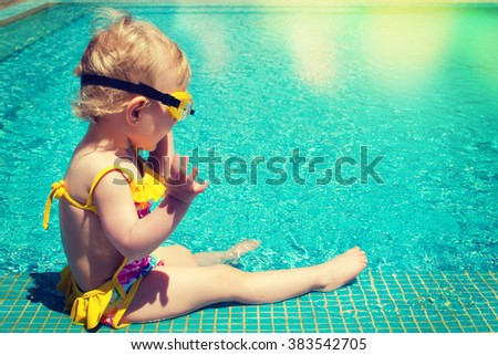 Baby sitting near swimming pool. - stock photo