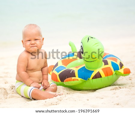 Baby sitting om the beach with swim ring - stock photo
