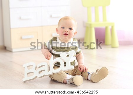 Baby sitting on a wooden floor