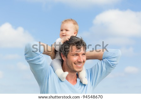 baby sitting on father - stock photo