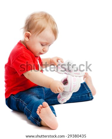 Baby sitting on floor and trying on trainers - stock photo