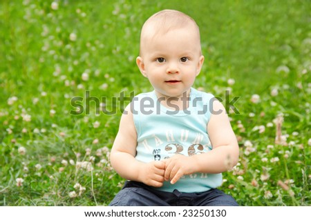 baby sitting on green grass - stock photo
