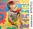 Baby sitting on play mat and chewing toy - stock photo
