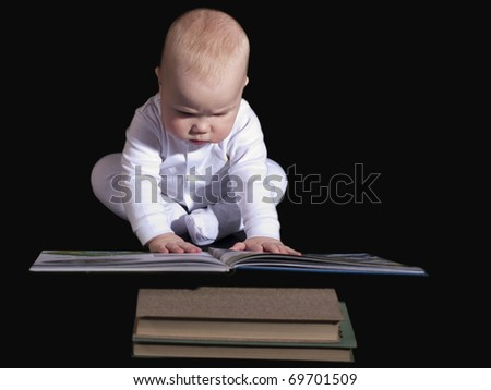 Baby sitting on the floor  and read a great book. - stock photo