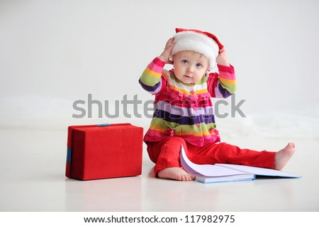 Baby sitting on the floor in a red santa hat. Kid holding his head. Christmas. On the floor is a book. - stock photo
