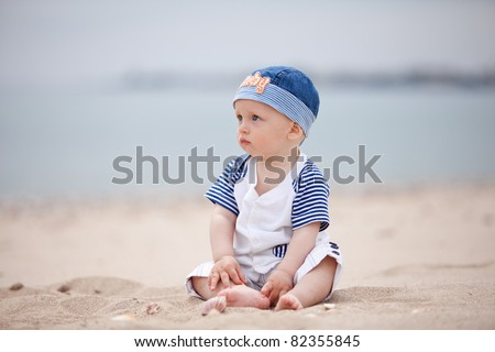 baby sitting on the sand at the beach - stock photo