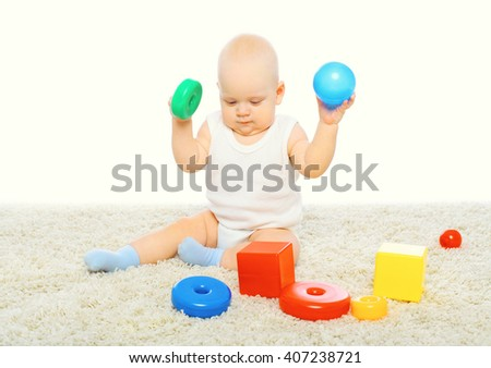 Baby sitting playing with colorful toys on background