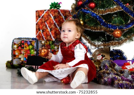 Baby sitting under a Christmas tree with gifts and christmas decorations