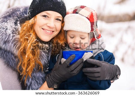 Baby sitting with young beautiful mother outside at snowy trees winter background and drinking hot tee. Happy family enjoying beautiful winter days on picnic. - stock photo