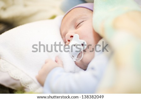 Baby sleep between sheets with pacifier. Tranquil scene with ambient light.