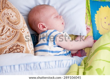 Baby sleep  in colored bed. - stock photo