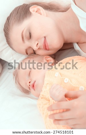 Baby sleep. Portrait of mother sleeping embracing her little child.  - stock photo
