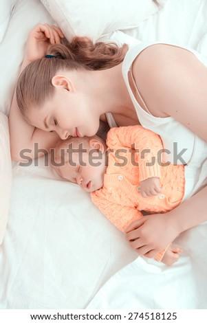 Baby sleep. Portrait of mother sleeping embracing her little child.  - stock photo