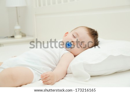 Baby sleeping comfortable with pacifier in bed after bottle of formula - stock photo