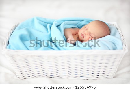 Baby sleeping in a basket - stock photo