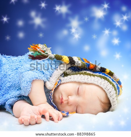 Baby sleeping in cute hat. Magic night sky background. - stock photo