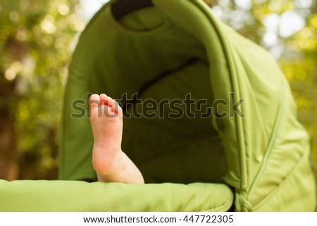 Baby sleeping in stroller outdoors. Small baby feet - stock photo