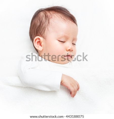 Baby sleeping on the white bed (isolated on white background) - stock photo