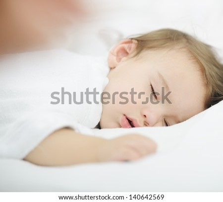 Baby sleeping on white bed with copy space